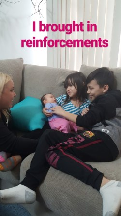 Two older cousins holding their baby cousin