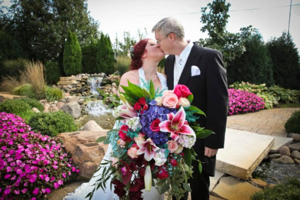 bride and groom kissing behind huge bridal bouquet
