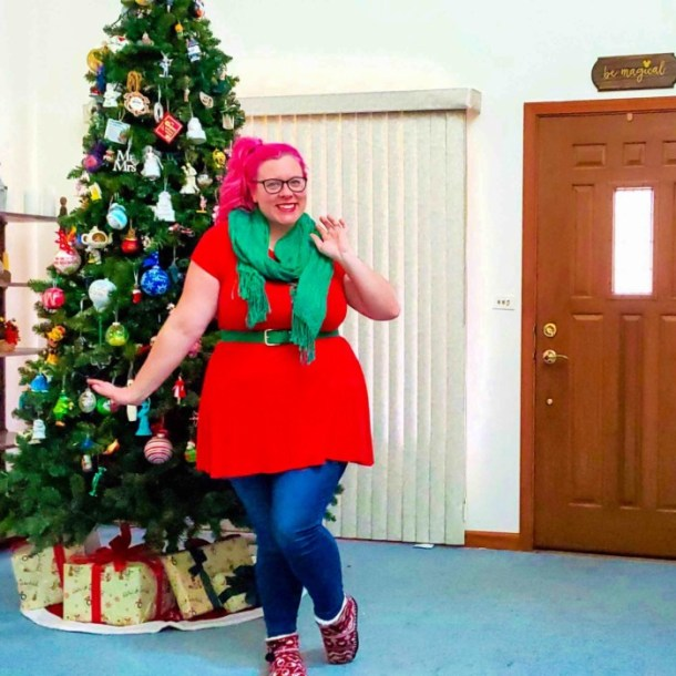 Chrissy in front of a Christmas tree wearing red and green