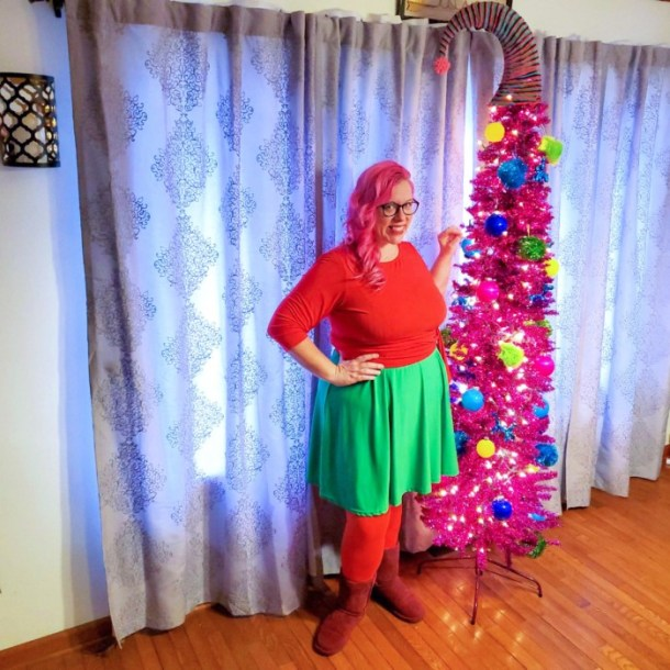 Chrissy in front of a pink Christmas tree wearing red and green