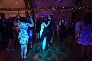 Wedding DJ at Nancarrow Farm, Truro, with bride and groom hugging in front of friends
