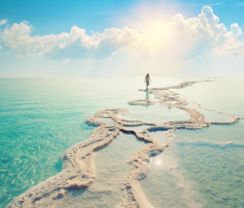 person walking on dried salt at Dead Sea