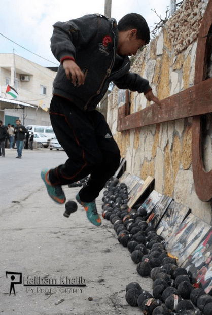 Child plays football with Israeli gas grenades