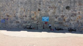 Migrants resting under the shade of a sign in the old port. This was one of the more comfortable sleeping places.