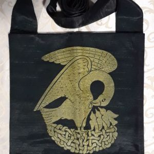Bag made from green-black fabric, lined, printed with a hand carved 15th century Pelican stamp in gold.