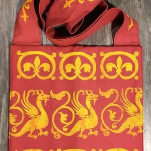 Bag made from red cotton fabric, lined with yellow cotton fabric & hand printed in yellow with a hand carved 13th century dragon and other medieval inspired stamps.