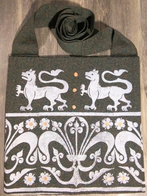 Lion bag made from green & brown patterned fabric, lined with black cotton fabric & hand printed with a hand carved 13th century lion & decorative border stamp.