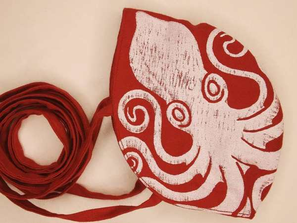 Red linen octopus face mask with long ties and white octopus print. New, pre-washed fabric, ready to wear and machine washable!