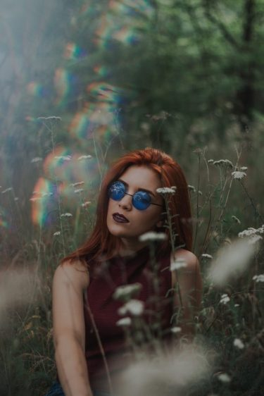Woman in blue glasses lying in a field of daisies, with rainbow light blurs around her. Purpose of image is to depict the different way neurodivergent people see the world.