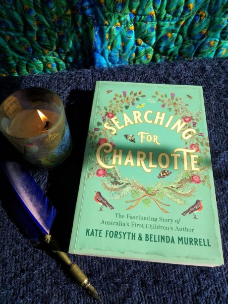 Book cover of 'Searching for Charlotte', with a lit candle and quill pen next to it.