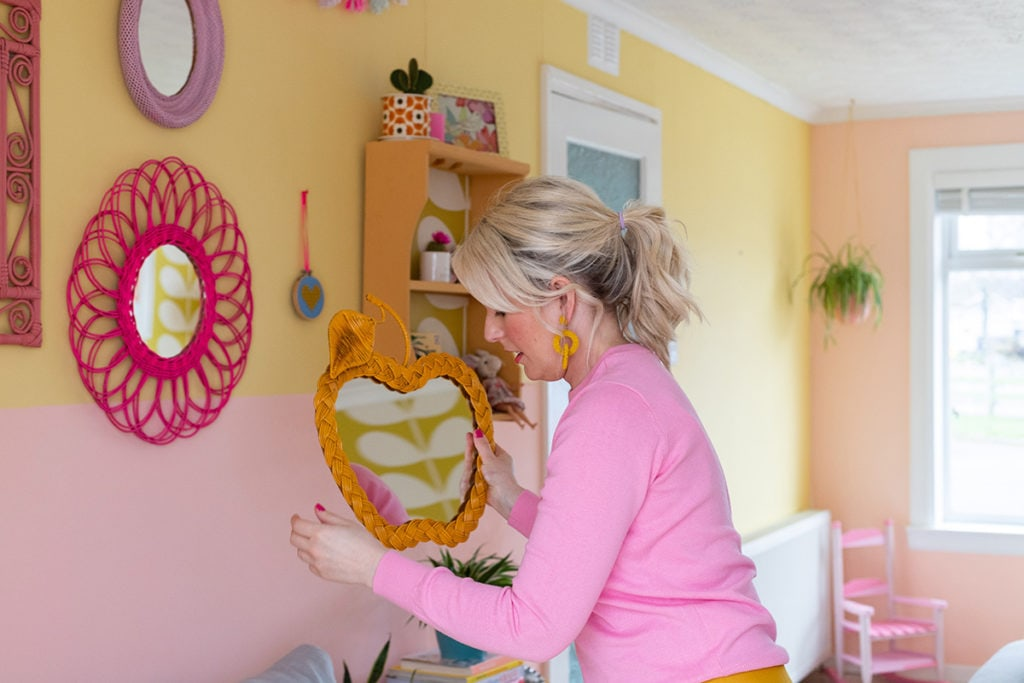 Rachel hanging an orange coloured apple-shaped wicker mirror on gallery wall