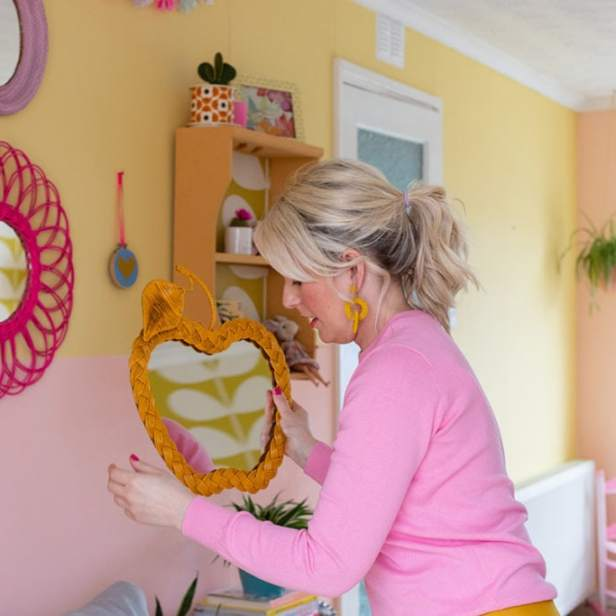Rachel hanging an orange coloured apple-shaped wicker mirror on gallery wall