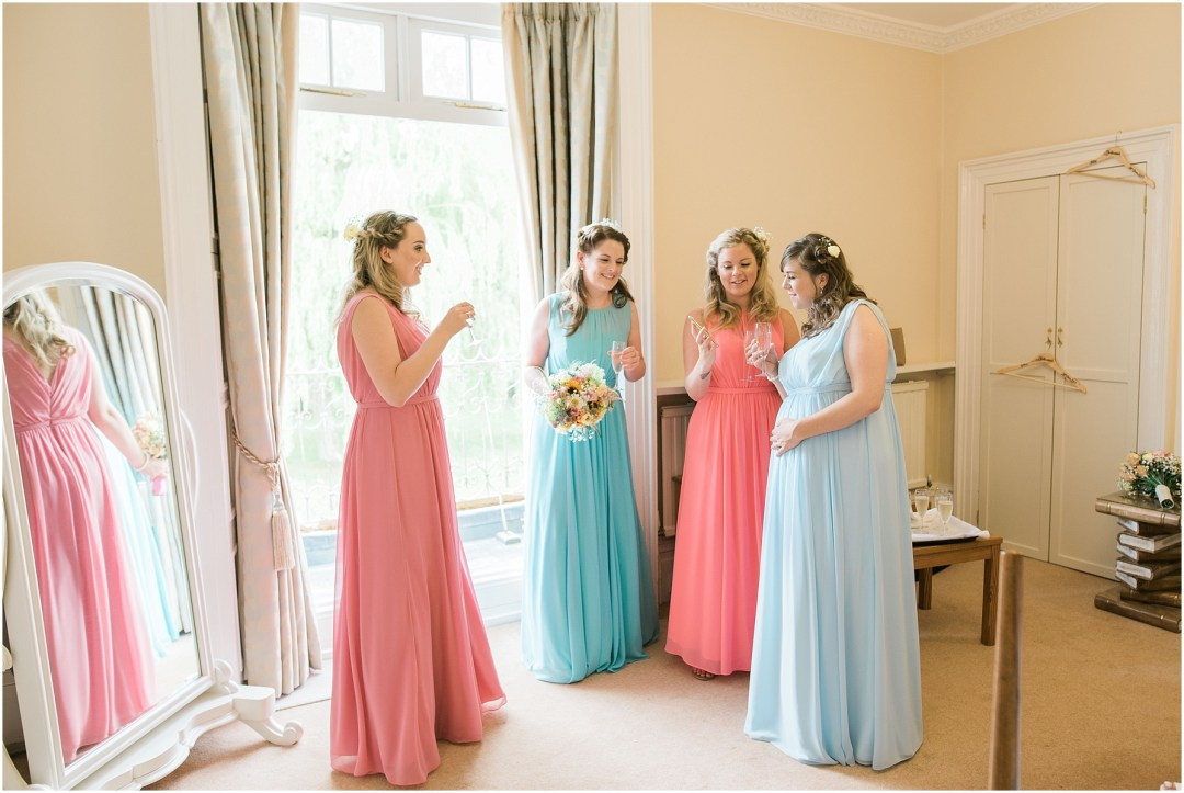bridesmaids drinking prosecco wearing pastel dresses