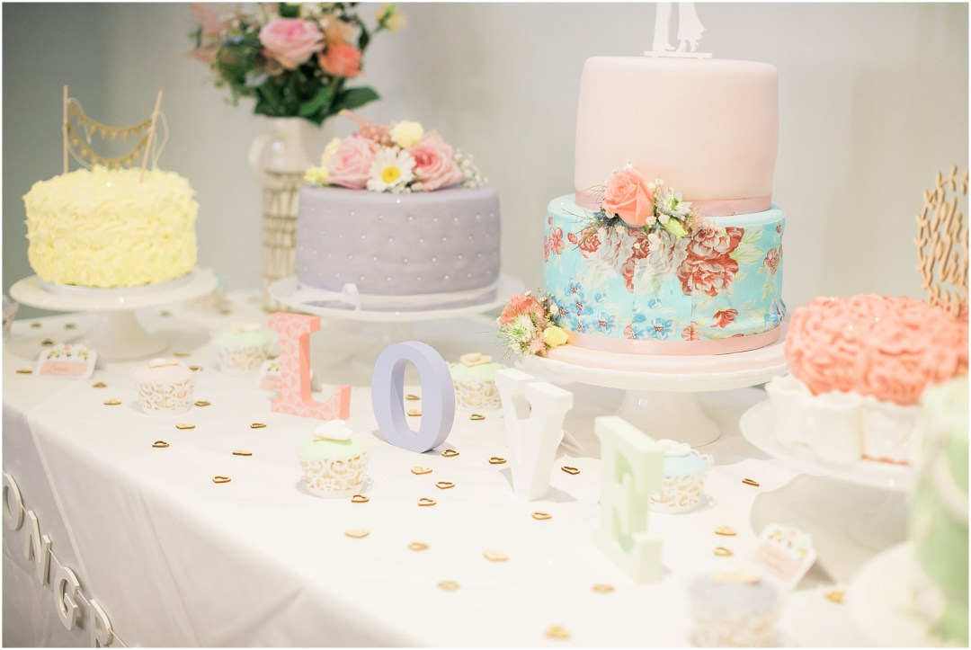 table of 5 pastel wedding cakes