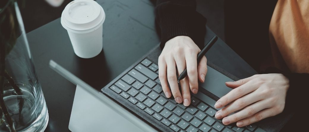 Hands typing on a keyboard beside a coffee cup