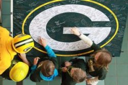 Frank Lamping, wearing the green and gold hard hat, is pictured with a niece and some of his nephews, as they look over a Packers flag filled with signatures of those who attended a pep rally in his honor on Friday.