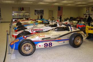 A line of classic Indy roadsters led off by the No. 98 car, the 1963 Agajanian Willard Battery Watson-Offy that Parnelli Jones drove.