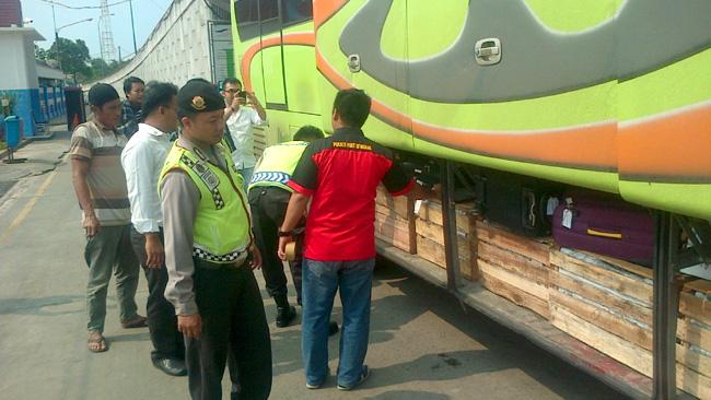 Petugas saat menggeledah bagasi bus