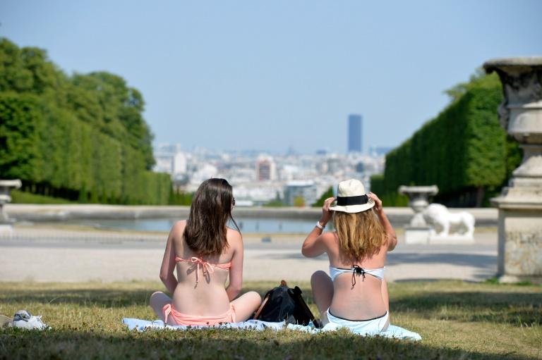 Deux femmes prennent le soleil à Saint-Cloud, le 1er juillet 2015. © AFP