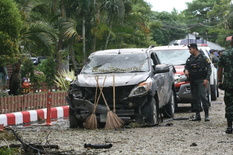 Un soldat thaïlandais inspecte une voiture carbonisée là où une bombe a explosé, à l'extérieur d'un hôtel dans la province de Pattani (sud), le 24 août 2016. © AFP