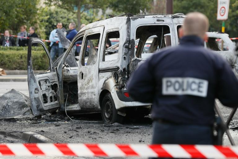 Un policier devant la carcasse d'un véhicule de police incendié à  Viry-Chatillon le 8 octobre 2016 . © AFP
