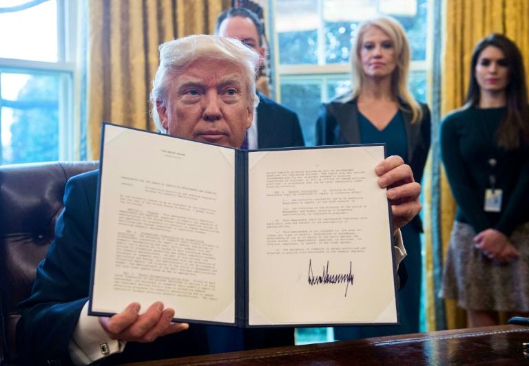 Le président Donald Trump montre l'un des décrets qu'il vient de signer, le 24 janvier 2017 dans le Bureau Ovale de la Maison Blanche, à Washington. © AFP