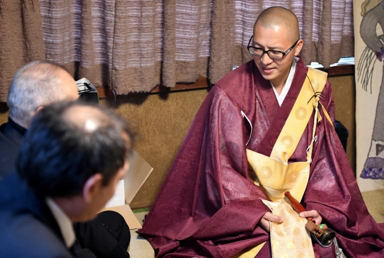 Kaichi Watanabe, un moine bouddhiste (D) s'entretient avec des particuliers lors d'une cérémonie à domicile à Funabashi, une banlieue de Tokyo le 10 novembre 2016 . © AFP