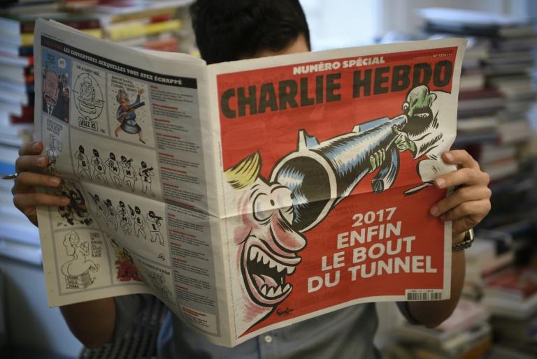 Un journaliste lit un numéro spécial de Charlie Hebdo à paraître mercredi, le 3 janvier 2017 à Paris. © AFP