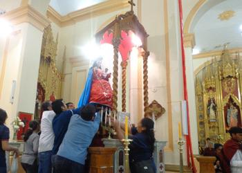 Los fieles y devotos bajan la imagen de Nuestra Señora del Rosario