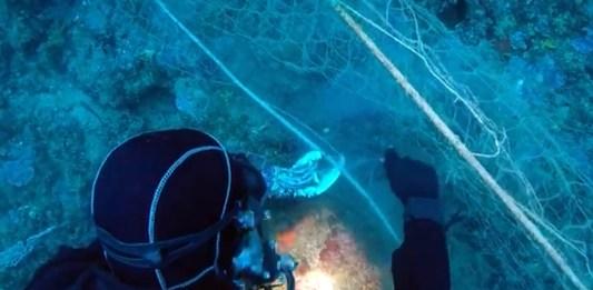 Un submarinista retirant la xarxa perduda a més de 50 metres de profunditat a la costa de Llafranc   Imatge dels Mossos d'Esquadra via ACN