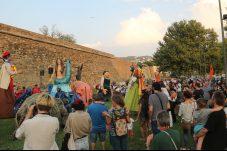 Pla mitjà de l'acte que s'ha fet aquest dissabte 25 de setembre de 2021 a Roses en contra del parc eòlic amb els gegants al fons. (Horitzontal)