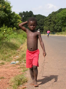 Boy walking on a road outside the capital, Bissau