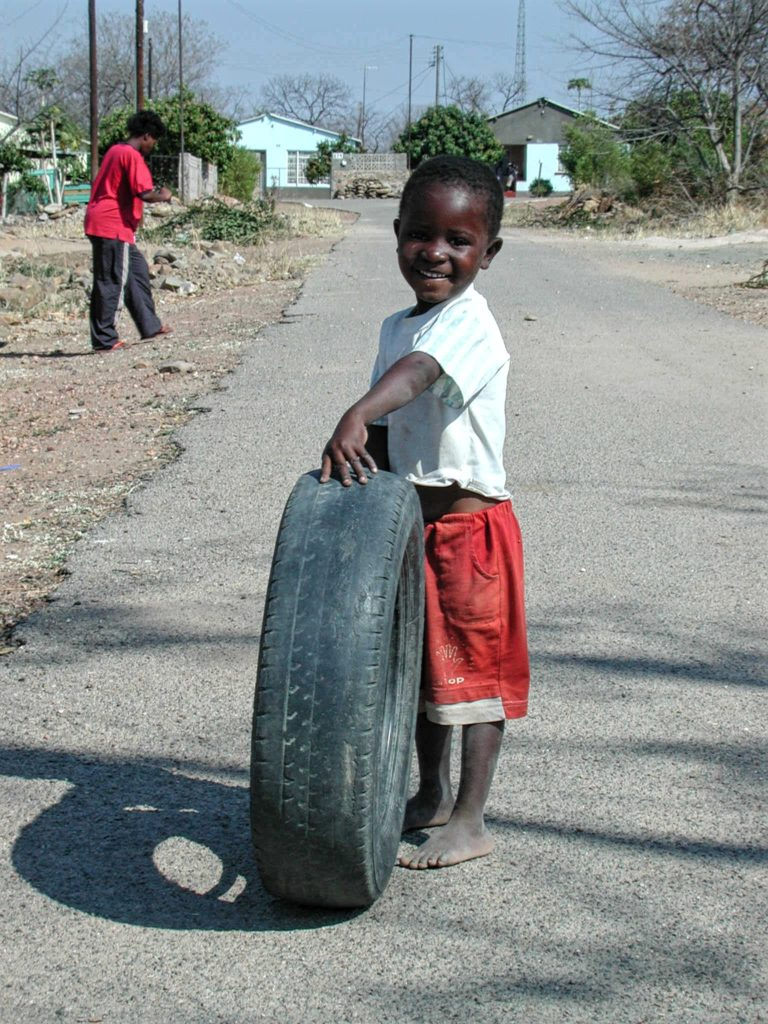 Child playing with a tyre
