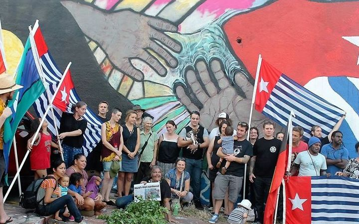 June Mills surrounded by supporters in front of her mural that was later painted over.