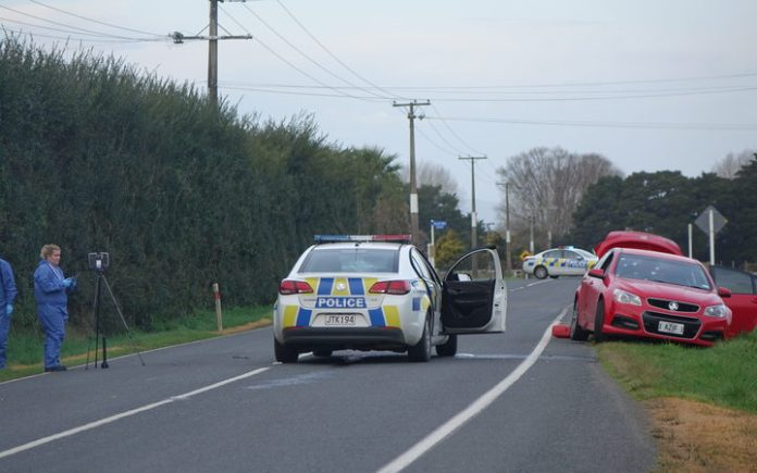 Police investigators at Kuranui Road today and the two cars involved in the incident.