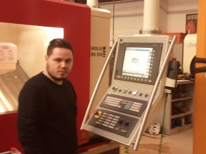 Un des étudiants devant une machine-outil à commande numérique