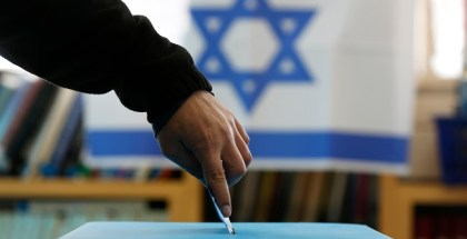 An Israeli flag is seen in the background as a man casts his ballot for the parliamentary election at a polling in the West Bank Jewish settlement of Ofra, north of Ramallah January 22, 2013. Israelis voted on Tuesday in an election that is expected to see Prime Minister Benjamin Netanyahu win a third term in office, pushing the Jewish state further to the right, away from peace with the Palestinians and towards a showdown with Iran. REUTERS/Baz Ratner (WEST BANK - Tags: POLITICS ELECTIONS TPX IMAGES OF THE DAY)