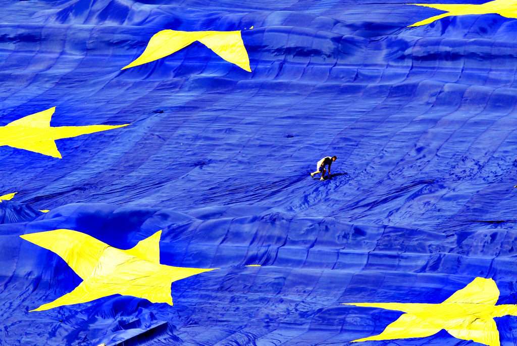 An organiser walks on a large European Union flag displayed in f