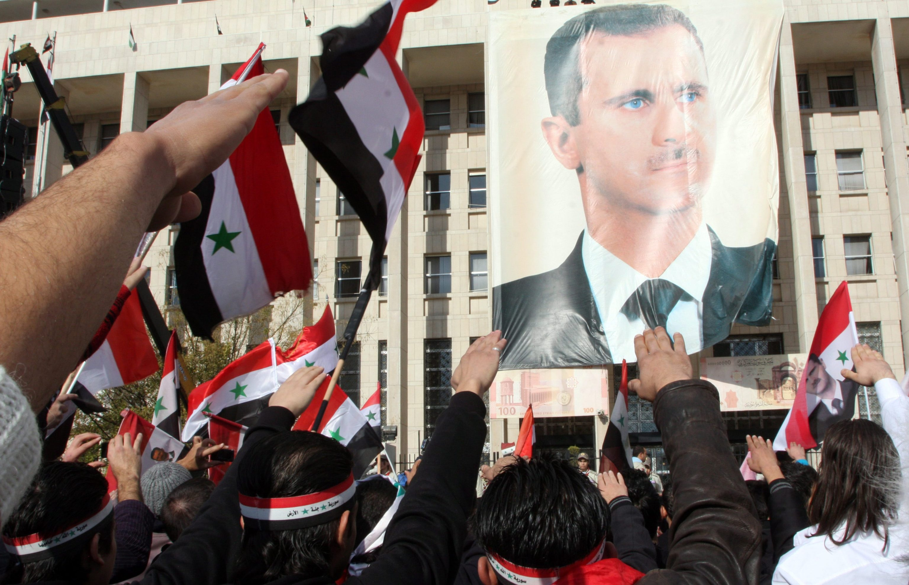 ansa - siria - epa03029257 Syrians shout pro-government slogans and wave national flags next to a poster of President Bashar Assad during a rally at Sabe Bahrat square in downtown Damascus, Syria, 09 December 2011. Thousands rallied in Damascus to show their support to President Bashar Assad after he denied in an interview on 07 December that he had ordered his troops to kill or attack civilians protesting against his rule and insisted he did not feel guilty for the bloodshed. In the meantime, opposition said on 09 December that at least six people were killed by Syrian security forces in the restive province of Homs. EPA/YOUSSEF BADAWI