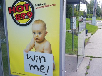 A radio station contest advertisement at a bus stop.