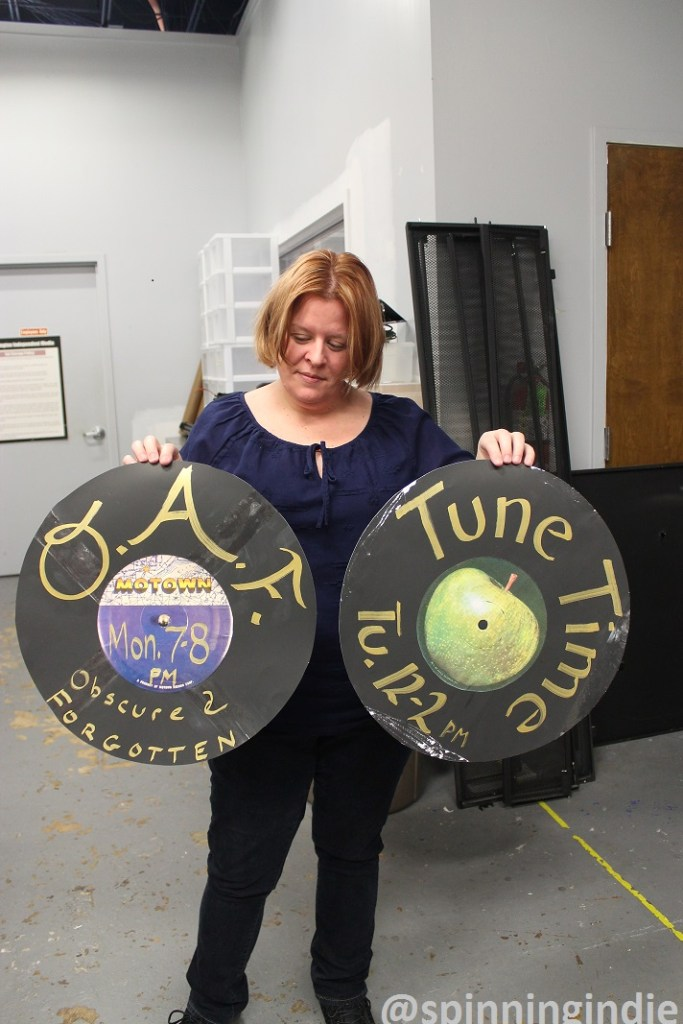 "Lauree McArdle showing promotional ""records"" for a few WERA-LP shows. Photo: J. Waits"
