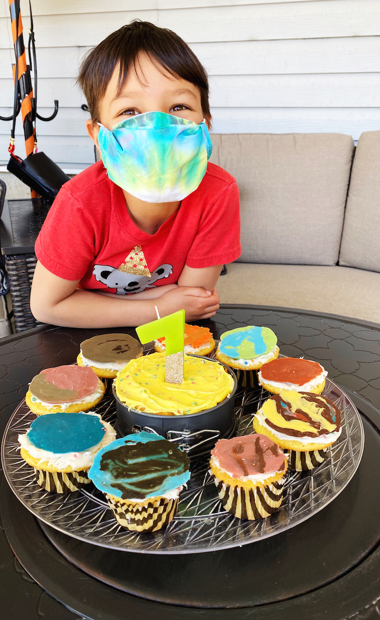 boy in mask with solar system cupcakes