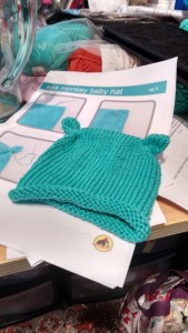 This picture contains a picture of a small green hat, atop its pattern called 'sea monkey baby hat'.
