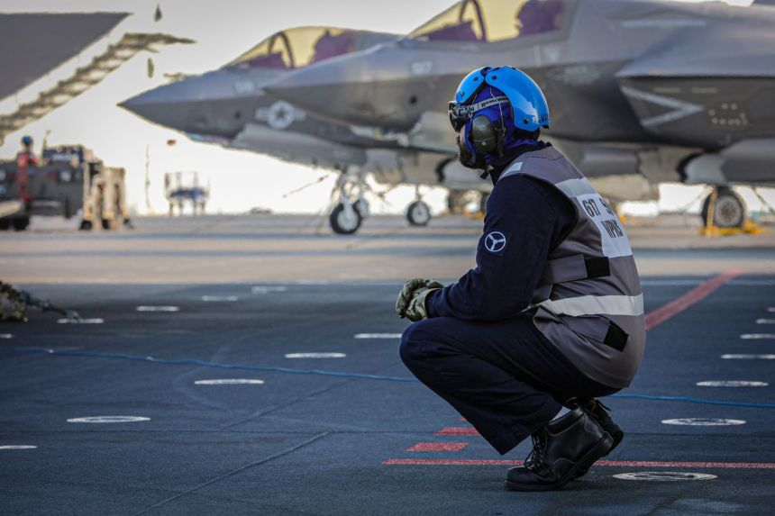 Image shows Royal Navy personnel with F35 aircraft in the background.