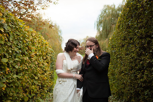 Laughing bride and groom stood between two hedges