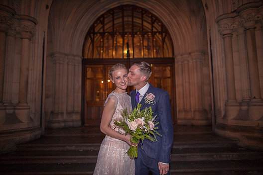 Groom kissing bride outside Manchester Town Hall