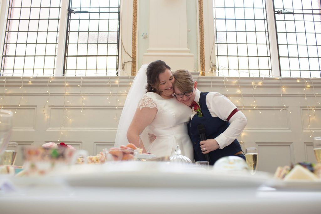 two brides embrace during wedding speeches