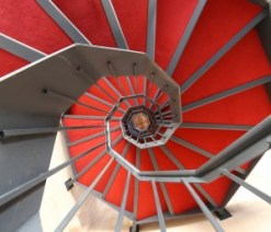 long spiral staircase with red carpet in a modern building