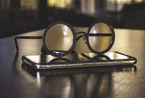 pair of beautiful eye glasses sitting on top of a smart phone