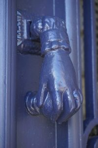 an ancient door knocker in blue - a hand reaching down to turn a door knob